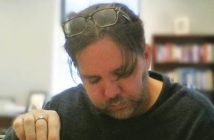 A close up of Brandon Hobson reading in a library with his glasses atop his head
