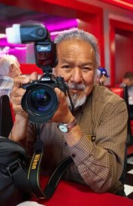 Durango Mendoza aims a camera at the viewer with a smile on his face