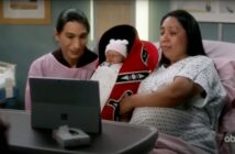 A Native couple hold a baby in a Tulalip cradleboard