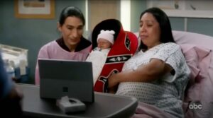 A male and female Native couple hold a baby in a red cradleboard in a screenshot from the television show Grey's Anatomy